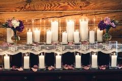 Decoração na tabela: velas nos vidros, flores roxas em uns vasos Fotografia de Stock