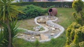 A decoração no parque De um grande jarro de volume de água e torna-se um córrego pequeno video estoque