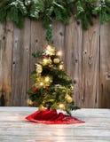 Decoração pequena da árvore de Natal na madeira rústica com backgr nevado imagem de stock