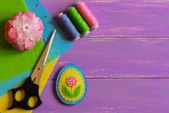 A decoração pequena do ovo da páscoa de feltro, grupo colorido da linha, almofada de alfinetes, tesouras, feltro liso cobre em um imagem de stock royalty free