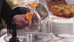 Decoração servida da tabela, garrafas do vinho, copos de vinho e placas Um homem está derramando um suco de fruta mixa em um copo filme