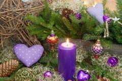 A decoração violeta ou roxa do Natal com uma vela e um vermelho faz Fotografia de Stock