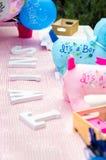 Decorações bem-vindas da festa do bebê na tabela Foto de Stock