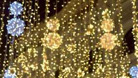Decorações bonitas douradas da cintilação das luzes de Natal da rua, fundo do borrão video estoque