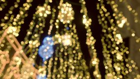 Decorações bonitas douradas móveis da cintilação das luzes de Natal da rua, fundo do borrão video estoque