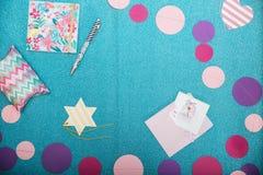 Decorações coloridas, bloco de notas, pena e caixa atual no backgound de brilho Imagem de Stock