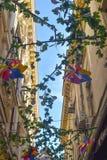 Decorações coloridas dos moinhos de vento e das flores contra o céu azul em uma rua estreita com construções velhas em Bucareste, imagens de stock