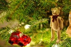 Decorações da árvore de Natal Carro vermelho pequeno que pendura na árvore do xmas Urso de peluche com curva vermelha Fotografia de Stock Royalty Free