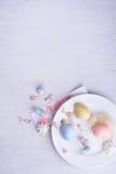 Decorações da cor pastel do feriado da Páscoa Ovos coloridos, sobremesa doce, orelhas do coelho Vista superior, espaço da cópia Fotos de Stock
