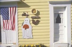 Decorações de Dia das Bruxas e uma bandeira americana em uma casa de madeira amarela Imagem de Stock Royalty Free