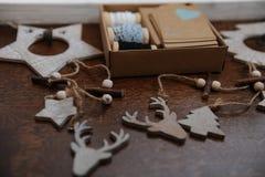 Decorações de madeira do Natal feitos a mão Cabeça de um cervo, de árvores de Natal e de estrelas Caixa de Kraft com fitas Imagens de Stock Royalty Free