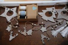 Decorações de madeira do Natal feitos a mão Cabeça de um cervo, de árvores de Natal e de estrelas Caixa de Kraft com fitas Fotografia de Stock Royalty Free