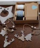 Decorações de madeira do Natal feitos a mão Cabeça de um cervo, de árvores de Natal e de estrelas Caixa de Kraft com fitas Imagem de Stock Royalty Free