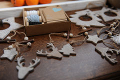 Decorações de madeira do Natal feitos a mão Cabeça de um cervo, de árvores de Natal e de estrelas Caixa de Kraft com fitas Imagem de Stock