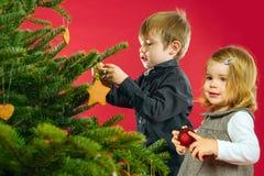 Decorações de suspensão da árvore de Natal do irmão e da irmã Fotografia de Stock Royalty Free