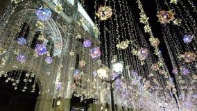 Decorações do ano novo da iluminação do Natal, cidade de brilho da rua da noite no centro, luzes brilhantes e bolas, bonitas filme