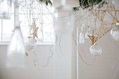 Decorações do ano novo sob a forma dos vidros e das estrelas de suspensão de vinho feitos à mão e o ramo da árvore de Natal Fotos de Stock