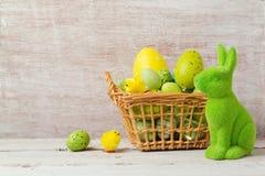 Decorações do feriado da Páscoa com os ovos na cesta e no coelho sobre o fundo de madeira Fotos de Stock