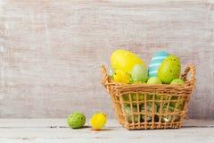 Decorações do feriado da Páscoa com os ovos na cesta sobre o fundo de madeira Imagens de Stock