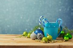 Decorações do Natal com o copo azul na tabela de madeira sobre o fundo sonhador do bokeh Foto de Stock