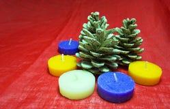 Decorações do Natal com vela, cone do pinho em um fundo vermelho Copie o espaço disponível para o conceito do xmas Imagens de Stock Royalty Free