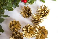 Decorações do Natal e cones dourados do pinho Fotografia de Stock Royalty Free