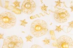 Decorações do Natal, estrelas do ouro, bolas e fitas no fundo de madeira branco macio, teste padrão, vista superior Foto de Stock