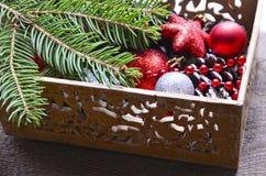 Decorações do Natal na caixa de madeira do vintage como uma preparação para decorar a árvore do xmas Foto de Stock