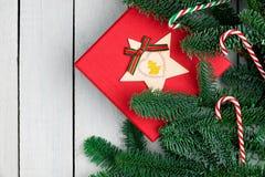 Decorações do Natal na mesa de madeira branca Configuração lisa Caixa de presente e candycanes vermelhos Ramos frescos do abeto d imagens de stock royalty free
