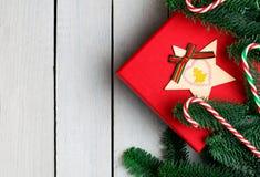 Decorações do Natal na mesa de madeira branca Configuração lisa Caixa de presente e candycanes vermelhos Ramos frescos do abeto d fotografia de stock royalty free
