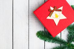 Decorações do Natal na mesa de madeira branca Configuração lisa Caixa de presente vermelha Ramos frescos do abeto da árvore de Na imagens de stock