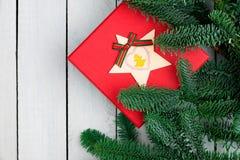 Decorações do Natal na mesa de madeira branca Configuração lisa Caixa de presente vermelha Ramos frescos do abeto da árvore de Na fotografia de stock royalty free