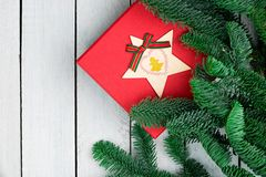 Decorações do Natal na mesa de madeira branca Configuração lisa Caixa de presente vermelha Ramos frescos do abeto da árvore de Na imagem de stock royalty free