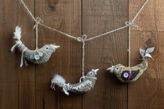 Decorações do Natal do pássaro da arte popular no fundo de madeira escuro Imagem de Stock