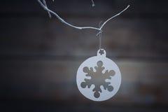 Decorações do Natal & x28; snowflake& x29; suspensão sobre o fundo de madeira Imagem de Stock