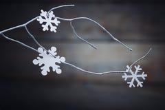 Decorações do Natal & x28; snowflake& x29; suspensão sobre o fundo de madeira Imagens de Stock Royalty Free