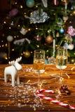 Decorações dos cervos do brinquedo do Natal na tabela com champanhe Foto de Stock