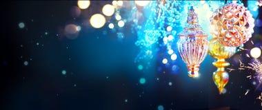 Decorações douradas do Natal e do ano novo sobre o fundo da noite piscar imagens de stock