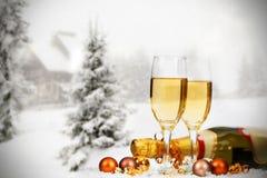 Decorações e champanhe do Natal contra o fundo do inverno Imagens de Stock