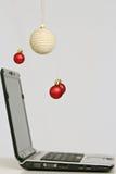 Decorações e portátil coloridos das bolas do Natal Imagens de Stock