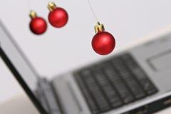 Decorações e portátil coloridos das bolas do Natal Foto de Stock