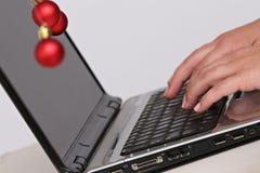 Decorações e portátil coloridos das bolas do Natal Fotos de Stock