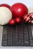 Decorações e portátil coloridos das bolas do Natal Fotografia de Stock
