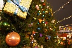 Decorações em uma árvore de abeto do Natal, luzes do Natal do fundo de um mercado do Natal em um quadrado vermelho, fotografia de stock