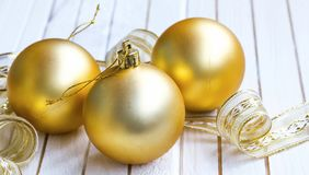 Decorações festivas douradas das bolas do Natal com a fita no branco Fotos de Stock Royalty Free