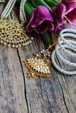 Decorações indianas para dançar: braceletes, colar Tulipas ultravioletas roxas no fundo de madeira rústico velho imagem de stock royalty free
