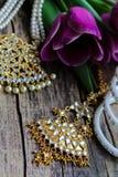 Decorações indianas para dançar: braceletes, colar Tulipas ultravioletas roxas no fundo de madeira rústico velho fotografia de stock