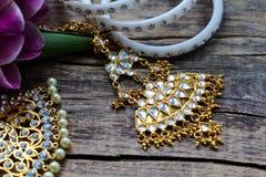 Decorações indianas para dançar: braceletes, colar Tulipas ultravioletas roxas no fundo de madeira rústico velho fotografia de stock royalty free