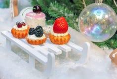 Decorações sob a forma de uma variedade de bolos no fundo da árvore de Natal fotografia de stock