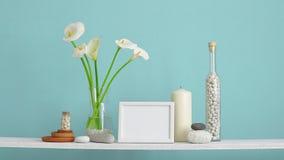 Decora??o moderna da sala com caixa Prateleira contra a parede de turquesa com cacto, vidro e as rochas decorativos M?o que coloc video estoque